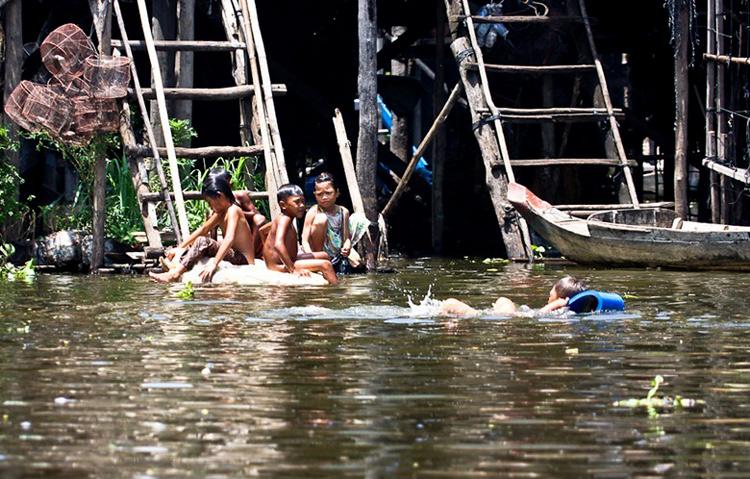 Những đứa trẻ ở làng nổi chơi đùa trên sông nước ở Kampong Phluk - Campuchia